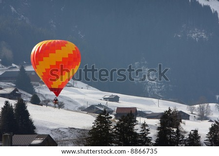 Colorful hot air balloon flying against a snow background - stock photo