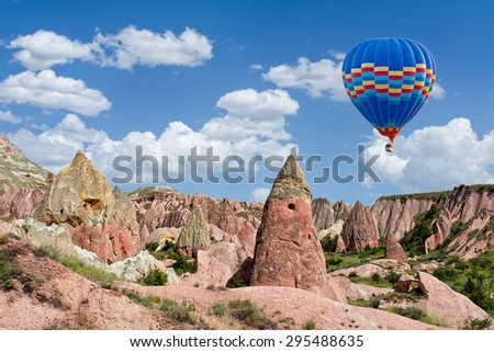 Colorful hot air balloon flying over Red valley at Cappadocia, Anatolia, Turkey. Volcanic mountains in Goreme national park. - stock photo