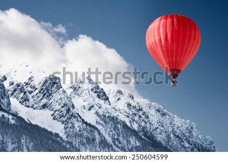 Colorful hot-air balloon flying over snowcapped mountain - stock photo