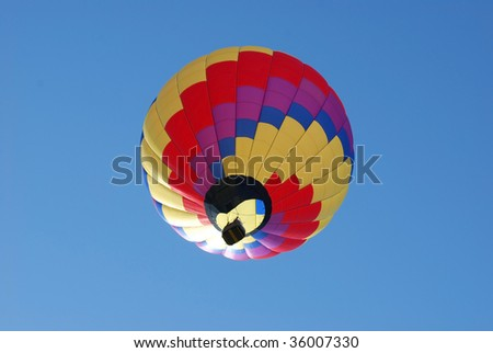 Colorful hot air balloon gently floating by against a clear blue sky. - stock photo