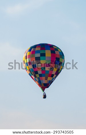Colorful hot air balloon in clear sky - stock photo