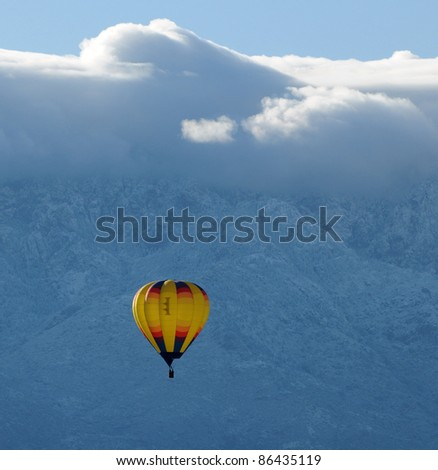 Colorful hot air balloon in midair against snowy mountain - stock photo