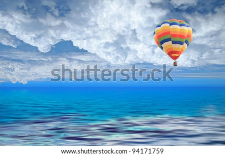 Colorful hot air balloon in the blue sky on sea - stock photo