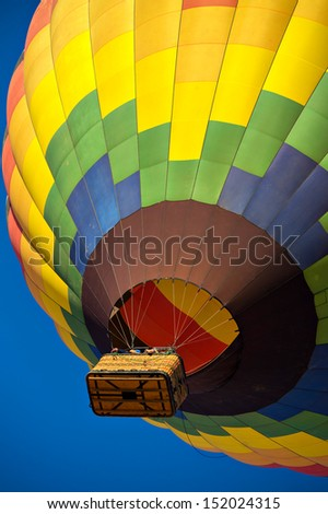 Colorful hot air balloon just after lift off.  Set against a deep blue sky. - stock photo