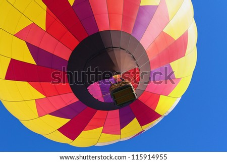 Colorful Hot Air Balloon moving up - closeup - stock photo