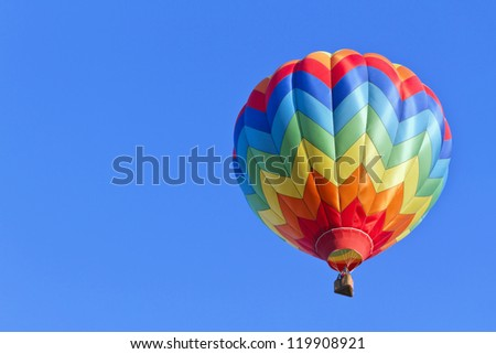 Colorful hot air balloon moving up in blue sky