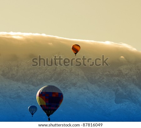 Colorful hot air balloon over a mountain top at dawn