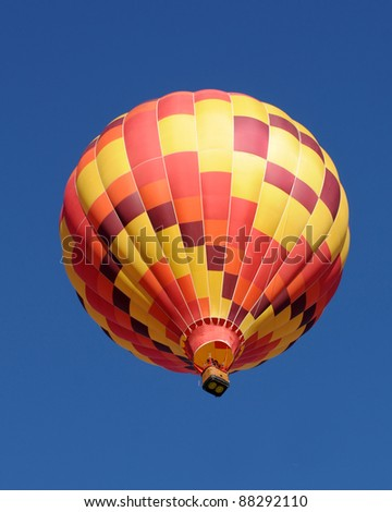 Colorful hot air balloon passing overhead - stock photo