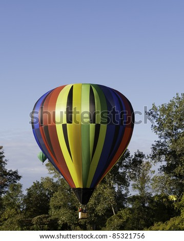 Colorful hot air balloon prepares to land. - stock photo