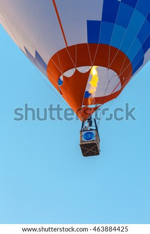 Colorful hot air balloon rises into the sky.