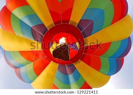 Colorful hot air balloon rising with flame burning.