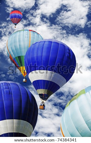 Colorful hot air balloon soaring into a cloudy blue sky. - stock photo