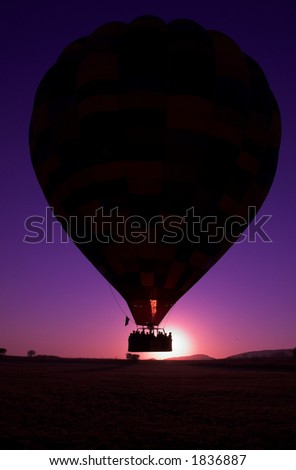 Colorful hot air balloon take off early in the morning with brilliant blue and purple sky - stock photo