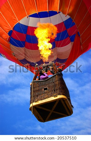 Colorful hot air balloon with bright burning flame - stock photo