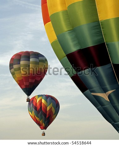 Colorful hot air balloons ascending against a cloud streaked sky. - stock photo