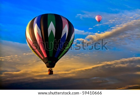 Colorful hot air balloons at sunset. Deep blue and gold sky and clouds. View from air as balloons float in the air current. - stock photo