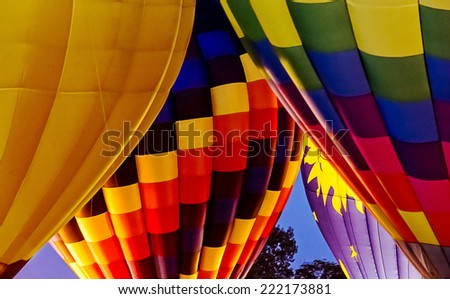 Colorful hot air balloons doing a night glow burn to light up the balloons for the crowd.  - stock photo