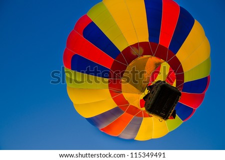 Colorful hot air balloons float up in the blue sky - stock photo