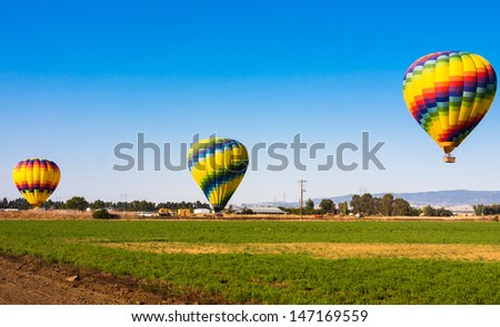 Colorful Hot Air Balloons flying above Fields - stock photo