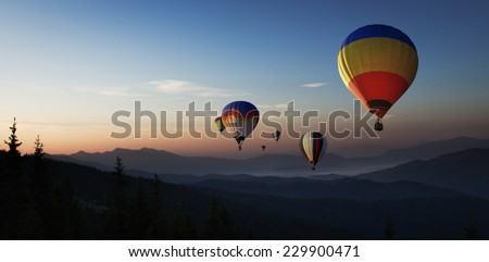 Colorful hot air balloons is flying at sunrise over the mountains - stock photo