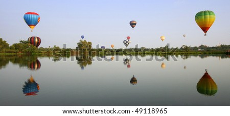 Colorful Hot Air Balloons launching over a lake in Ayuthaya, Thailand - stock photo