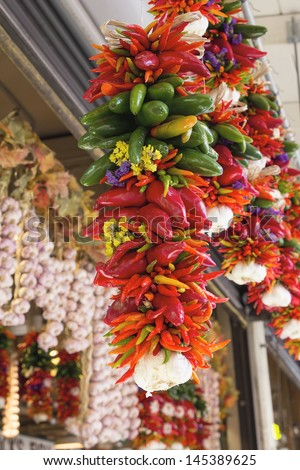 Colorful Hot Chili Jalapeno and Cayenne Peppers and Garlic Bunches Hanging at Fruits and Vegetable Stall - stock photo