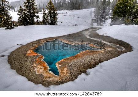 Colorful hot mineral springs in Yellowstone National Park during wintertime. - stock photo