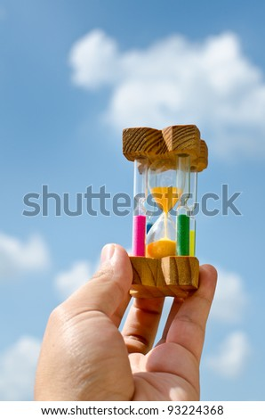 Colorful hourglass sand timer in hand of man on the sky - stock photo