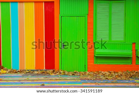 Colorful house. Bright colorful wall facade with green door and wooden window - stock photo