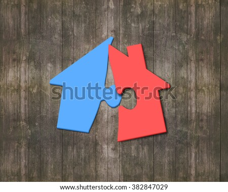 Colorful house shape puzzles, on brown wooden wall background.