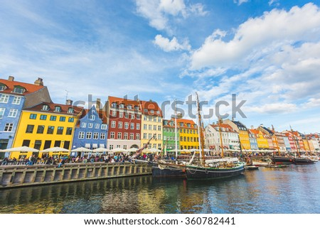 Colorful houses in Copenhagen old town, with boats and ships in the canal in front of them and unrecognizable people on the footpath. Travel destination and architecture  in Denmark - stock photo