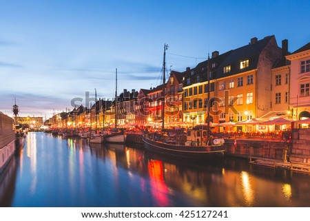 Colorful houses in Copenhagen old town, with boats and ships in the canal in front of them. Long exposure shot at night. Travel and architecture concepts