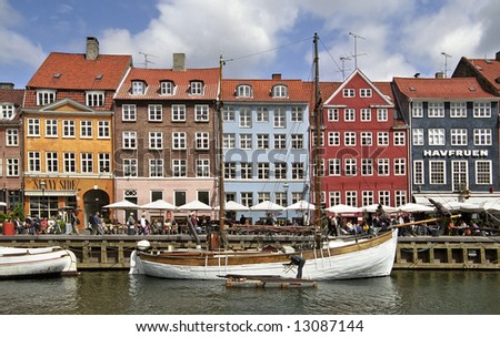 Colorful houses in Copenhagen wit a lot of tourists - stock photo
