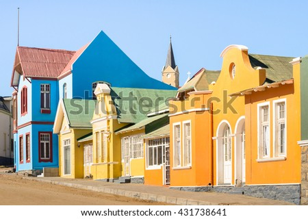 Colorful houses in Luderitz - Architecture concept with ancient german style town in south Namibia - Exclusive travel destination in african european settlement - Warm afternoon color tones - stock photo