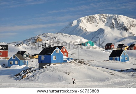 Colorful houses in the Kulusuk village and walking person, Greenland - stock photo