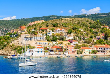 Colorful houses of Assos village and yacht boats in port on Kefalonia island, Greece