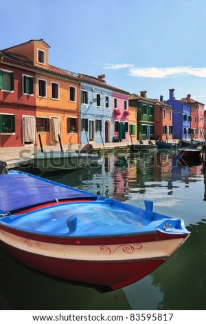 Colorful houses of Burano with a bright-colored boat in the foreground - stock photo