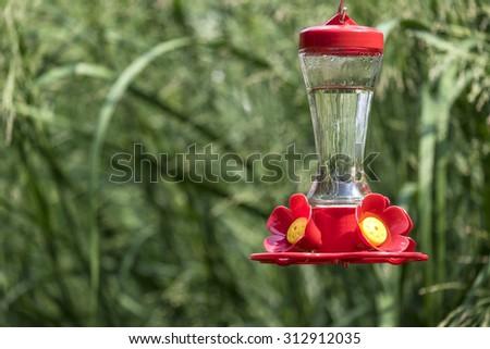 Colorful Hummingbird Feeder in a Backyard  Garden - stock photo