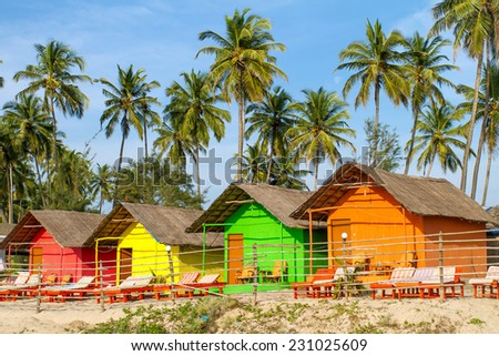 Colorful huts on the sandy beach with palm trees background in Goa, India - stock photo
