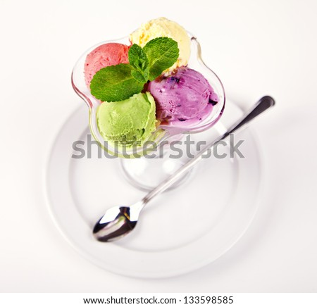 Colorful ice cream balls in bowl with spoon on white background - stock photo