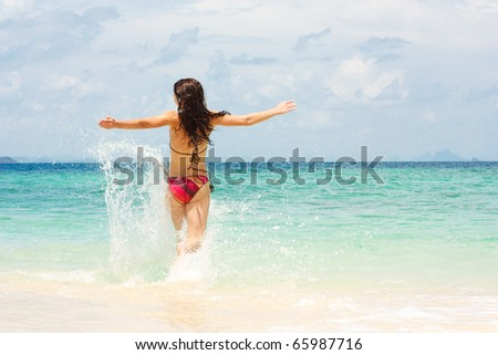 Colorful image of woman running into ocean - stock photo
