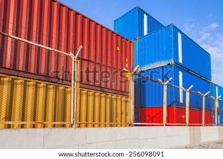 Colorful industrial cargo containers are stacked under blue cloudy sky behind metal fence with barbed wire - stock photo
