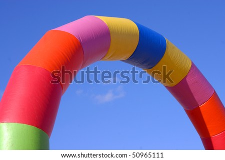 Colorful inflatable arch shaped tube on blue sky background