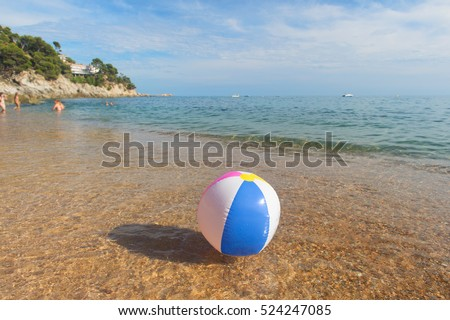 Colorful inflatable beach ball playing with the surf and the sea