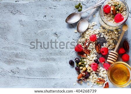 Colorful ingredients for breakfast or smoothie (berries, nuts, oat flakes, dried fruits, honey) over concrete textured background, place for text, top view. Healthy food, Diet, Detox, Clean Eating. - stock photo