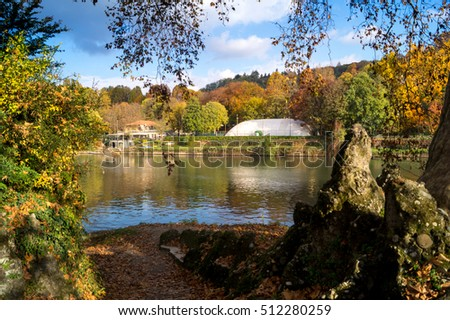 Colorful italian park with trees and autumn colors and water