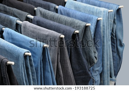 Colorful jeans hanging on hangers. - stock photo