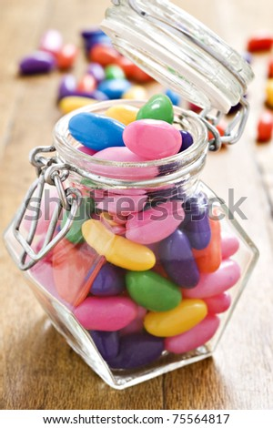 Colorful jelly beans in a bottle - very shallow depth of field - stock photo
