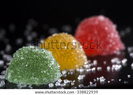 Colorful jelly candies with sugar over dark background - stock photo