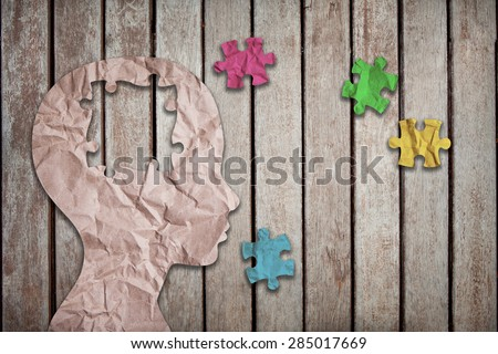 colorful jigsaw puzzle pieces and wrinkled paper project as a outline of children head on wood background - stock photo